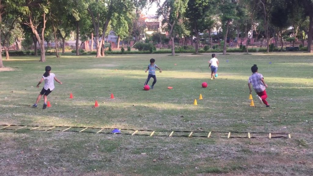 Little kids doing agility and football together